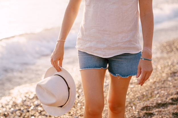 Woman in shorts with a hat in her hand walks along a pebble beach near the water