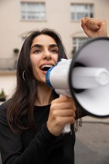 メガホンに向かって叫ぶ女性のクローズアップ
