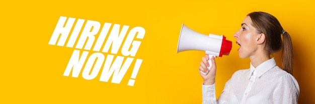 Woman shouts into a megaphone on a yellow background