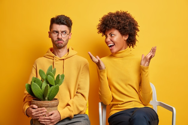 Woman shouts loudly at husband sort out relationships at home pose on chairs