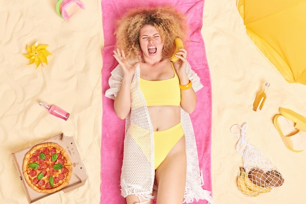 Woman shouts loudly keeps ripe banana near ear wears yellow bikini and beach wrap poses on pink towel spends free time at seaside during sunny day