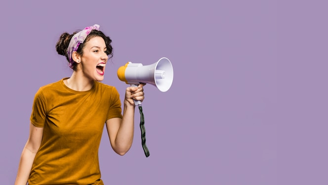 Woman shouts in megaphone with copy space