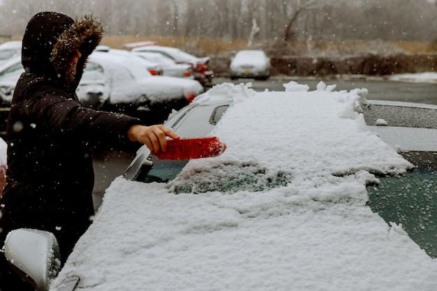 女性のシャベルと彼女の車から雪を取り除く雪を立ち往生