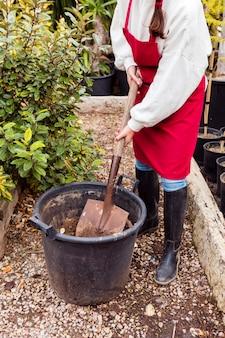 Woman shoveling in large pot