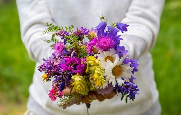 女性は、さまざまな花と色の自然な花の花束を示しています-自然と環境の概念-自由と幸福の概念のライフスタイルのための人々とデイジー
