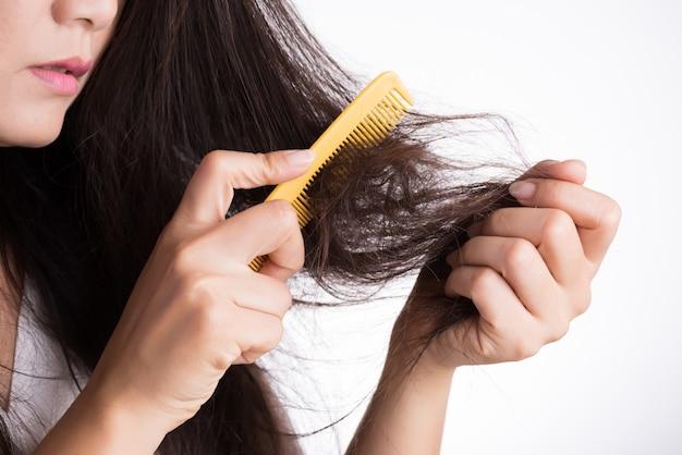 여자는 손상된 긴 손실 머리를 가진 그녀의 브러쉬를 보여