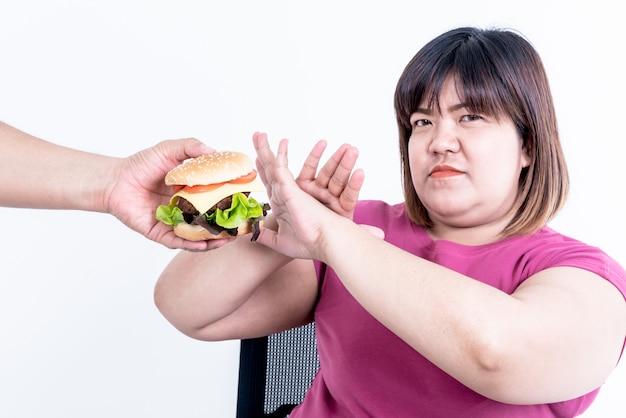 Женщина показывает признаки отказа от гамбургера