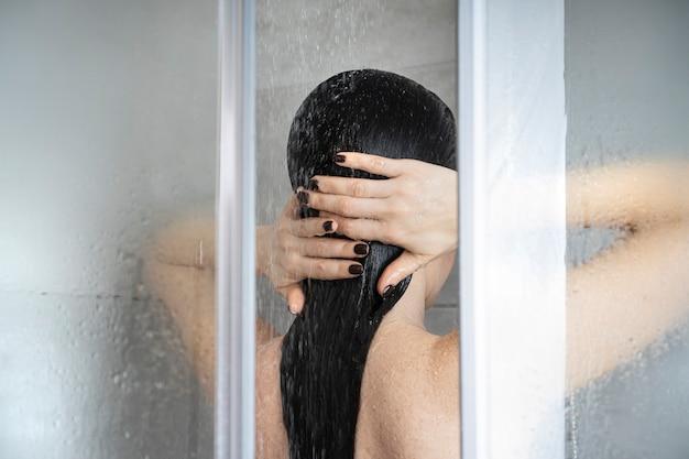 Женщина принимает душ. взрослая девушка принимает душ в душевой кабине. вид сзади. домашний фон лечения спа.