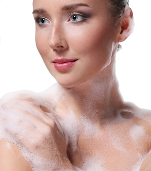 Woman showering with soap on the body and head. hygiene and skin care concept