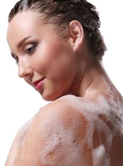 Donna che fa la doccia con sapone sul corpo e sulla testa. concetto di igiene e cura della pelle