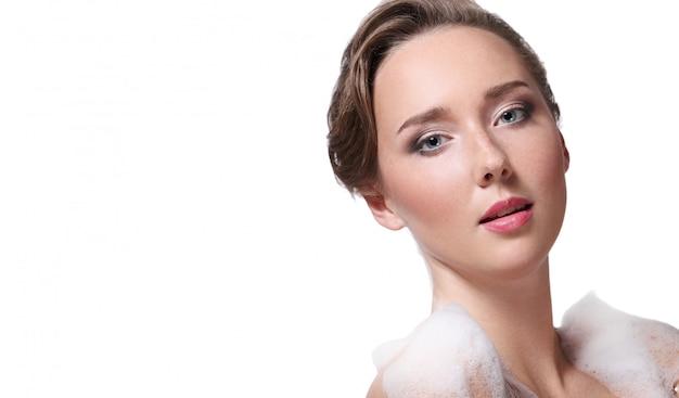 体と頭に石鹸でシャワーを浴びている女性。衛生とスキンケアのコンセプト