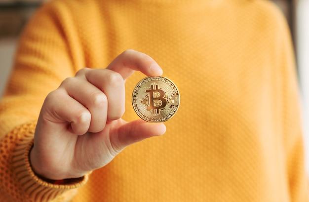 彼女の手にビットコインを示す女性