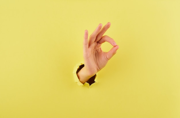 Женщина показывает знак согласия на желтом фоне копирования пространство крупным планом