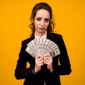 黄色の背景に分離された彼女の指でお金のスタックを示す女性。