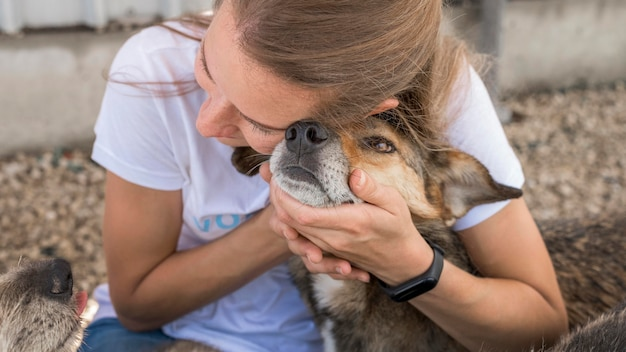 Woman showing affection to rescue dog at shelter