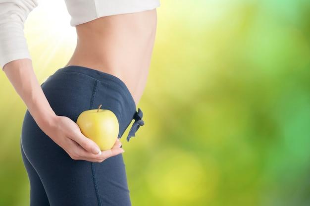 お腹のクローズアップでリンゴを示す女性