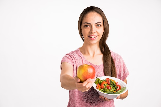 Woman showing an apple and holding a salad