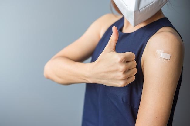 Женщина показывает руку с повязкой после вакцинации от covid 19