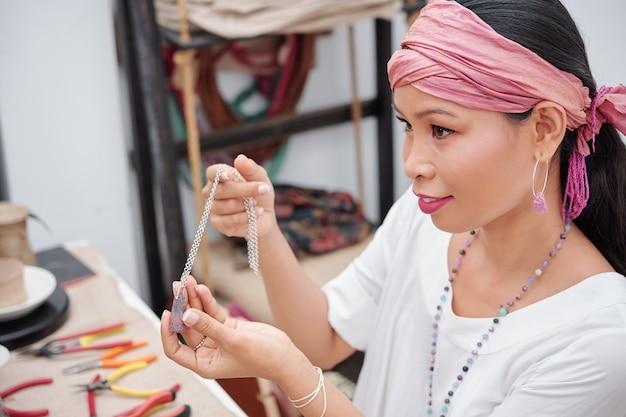 Женщина показывает красивое ожерелье