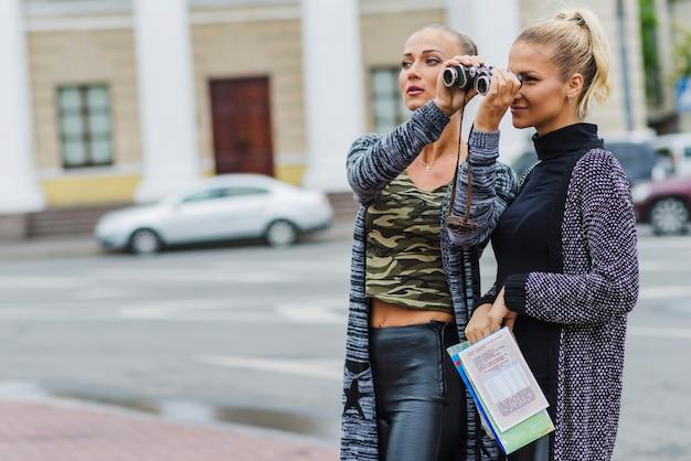 Женщина показывает бинокль другу Бесплатные Фотографии