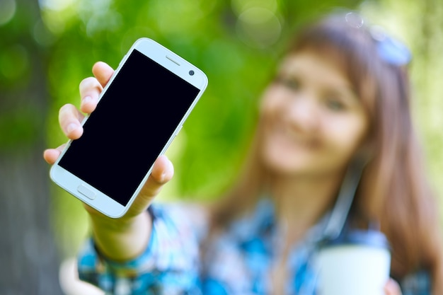 Woman showing blank phone screen and gadget accessories in park