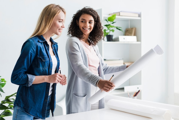 Woman showing blond female coworker paper sheet