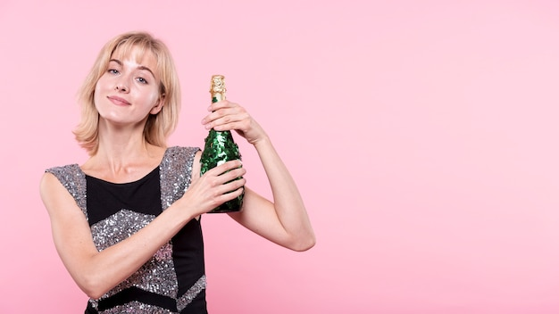 Woman showing a bottle of champagne on pink background