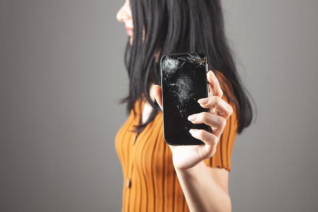 灰色の背景に壊れた電話画面を示す女性