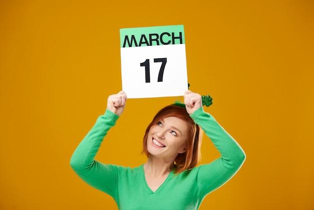 성 패트릭의 날 날짜가 표시된 달력을 보여주는 여성