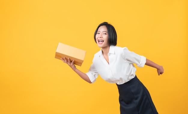 Женщина показывает картонные коробки на желтом фоне