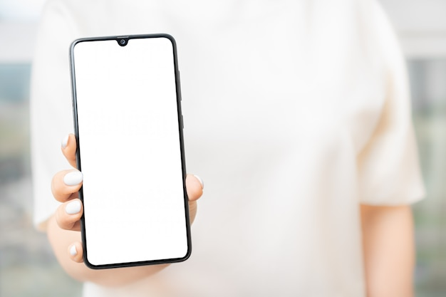 Woman showing cell phone with blank screen. mockup