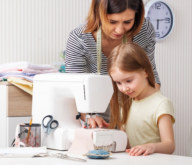 Woman showing to child how to sew at home