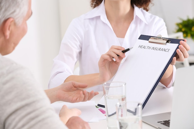 Woman showing clipboard and pointing at advantages of health insurance