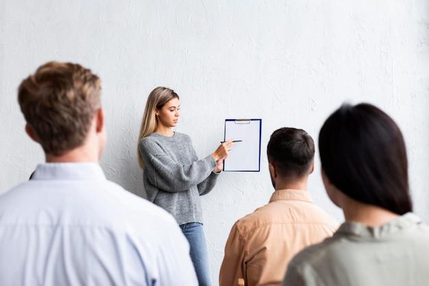 集団療法セッションで人々とクリップボードを示す女性