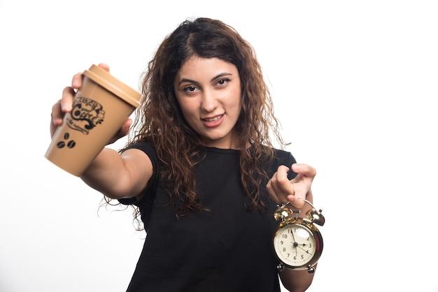 白い背景の上の時計とコーヒーのカップを示す女性。高品質の写真