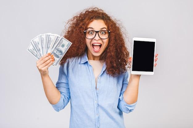 タブレットコンピュータのディスプレイを表示し、お金を保持している女性