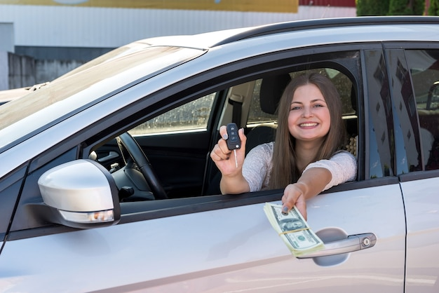 자동차 창에서 달러와 키를 보여주는 여자