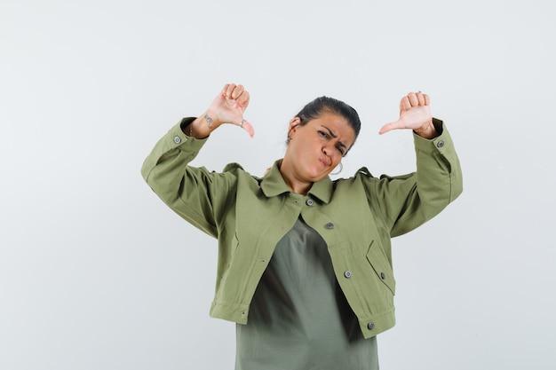 여자 재킷, t- 셔츠에 아래로 두 엄지 손가락을 보여주는 우울한 찾고