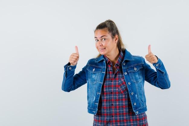 シャツ、ジャケットで二重の親指を見せて、嬉しそうに見える女性。正面図。