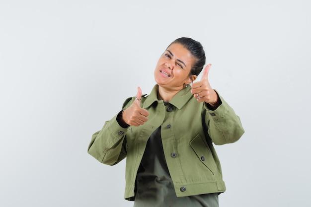 Donna che mostra i doppi pollici in su in giacca, t-shirt e sembra sicura