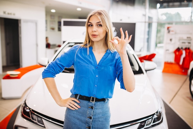 Woman showing emotions standing in front of a car