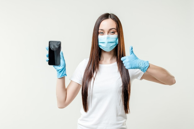 Woman showing empty copy space phone screen wearing mask and gloves