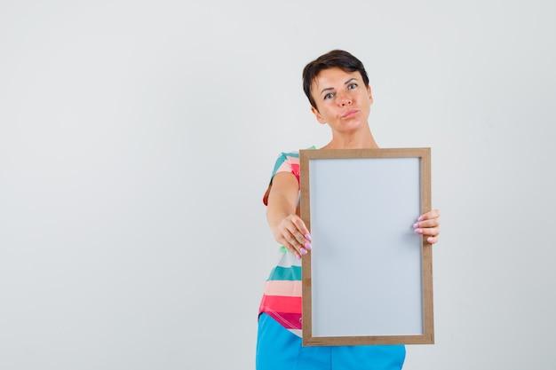 縞模様のtシャツ、パンツで空のフレームを示す女性