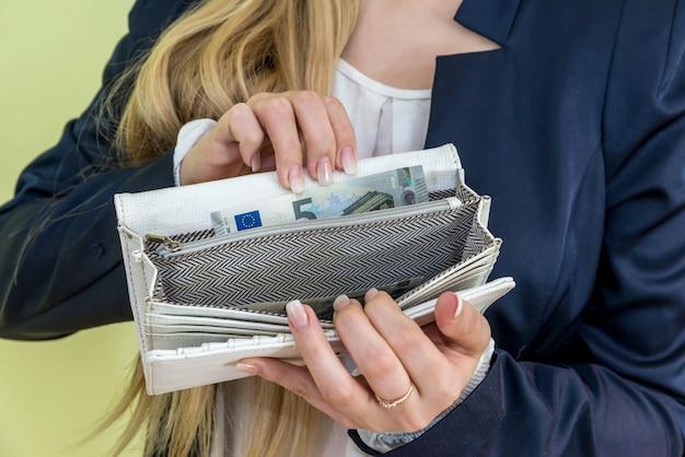 緑に空の財布を示す女性