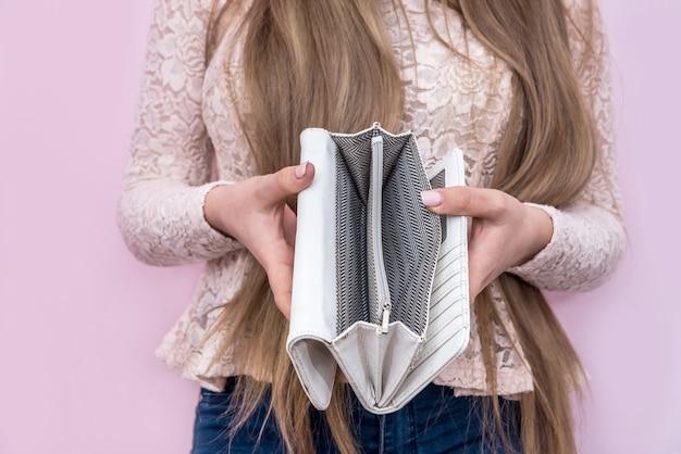Женщина показывает пустой бумажник на розовой стене