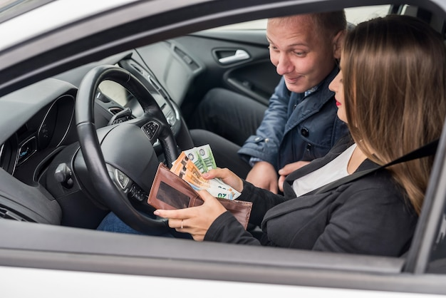 Woman showing euro banknotes in wallet sitting in car