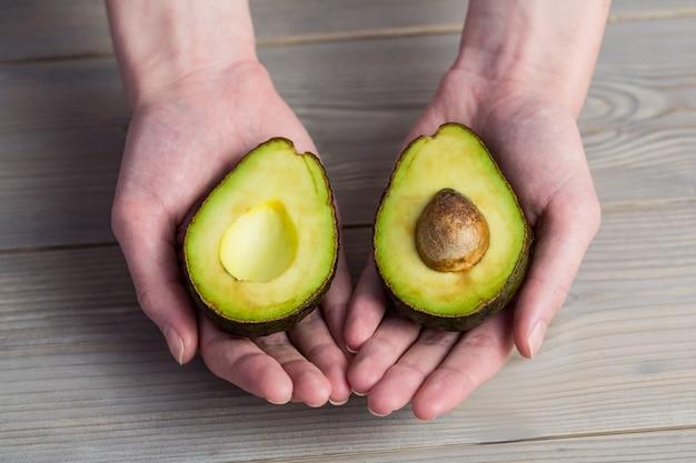 Женщина показывает свежий авокадо