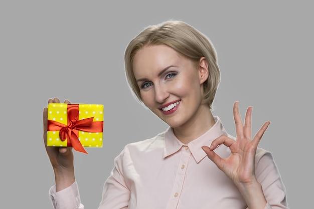 선물 상자와 확인 표시를 보여주는 여자. 회색 바탕에 선물 상자를 들고 꽤 웃는 여자. 특별 휴가 상품.