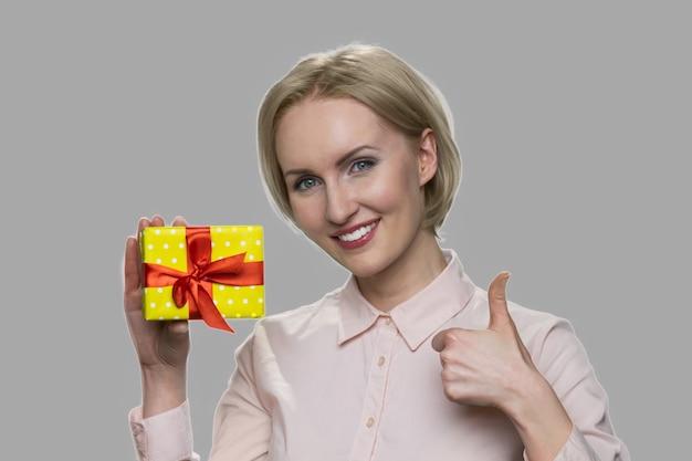 선물 상자와 엄지 손가락을 보여주는 여자. 선물 상자를 들고 승인 기호를주는 행복 한 웃는 여자. 회색 배경에 고립.