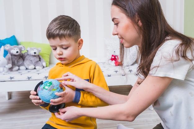 Donna che mostra globo al figlio